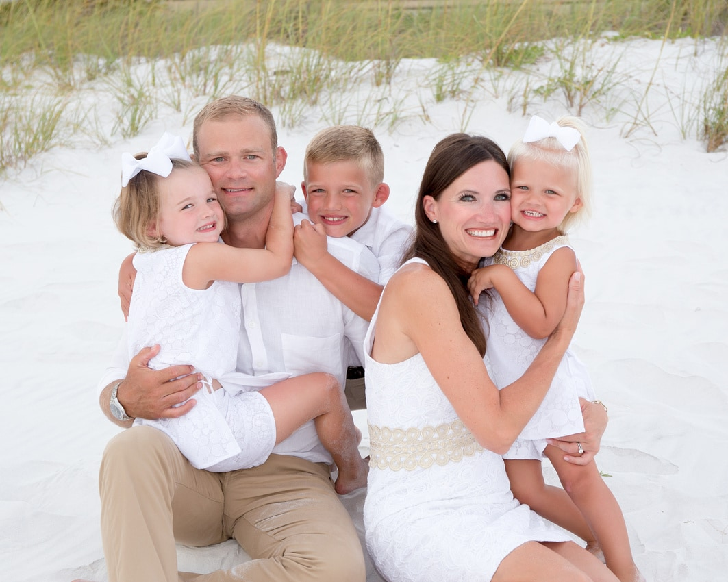 family wearing white on the beach
